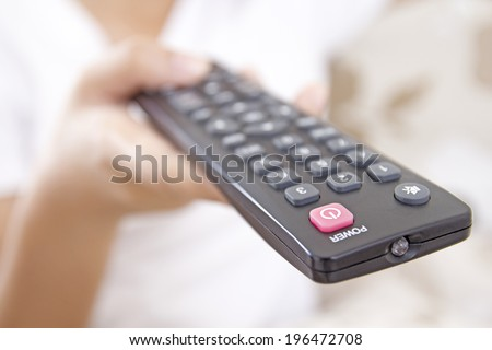 Close up of a hand holding a television remote control. - stock photo