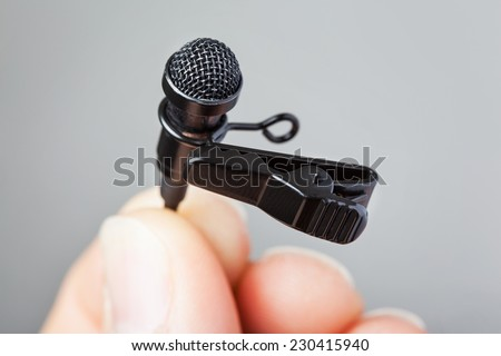 Close-up of a hand holding a tie-clip microphone against a plain background - stock photo