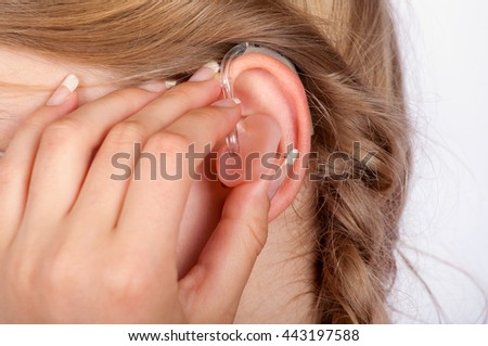 Close-up of a hand inserting a hearing aid in the ear - stock photo