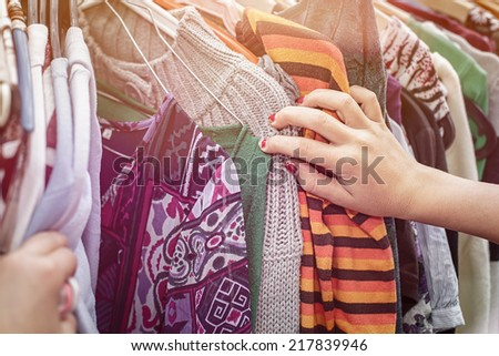 close up of a hand, looking on a flea market for clothes.