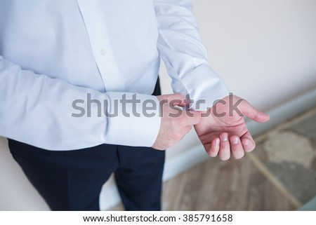 close up of a hand man how wears white shirt and cufflink
