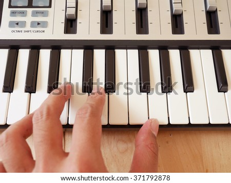 Close up of a hand playing a MIDI controller keyboard.