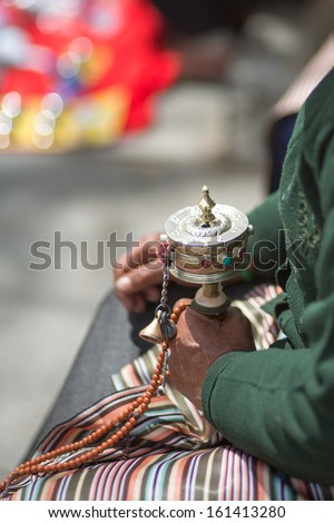 Close up of a hand praying with prayer roll at the Palkhor Monastery in Lhasa. Tibet 2013 - stock photo