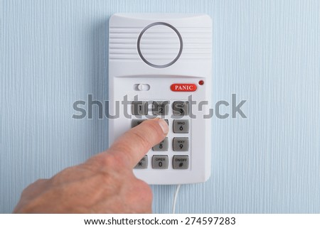Close-up Of A Hand Pushing Button In Security System