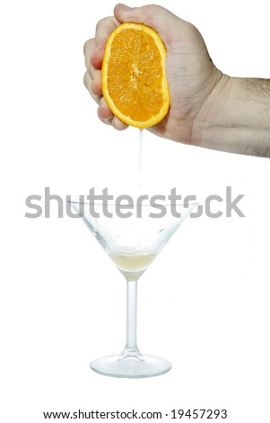 Close-up of a hand squeezing an orange making homemade orange juice. - stock photo