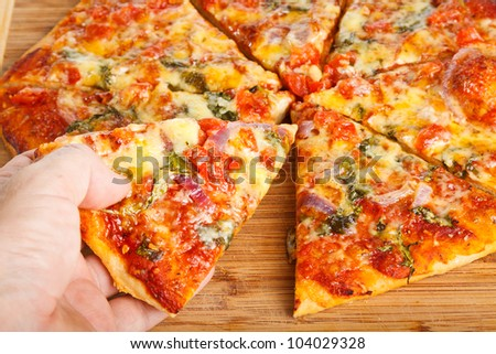 Close-up of a hand taking a slice of homemade pizza - stock photo