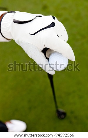 Close-up of a hand wearing a glove and holding a golf club - stock photo