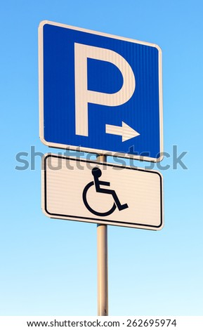 Close-up of a handicapped parking sign against blue sky - stock photo