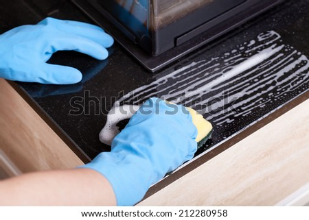 Close-up of a hands in rubber gloves cleaning the fireplace - stock photo