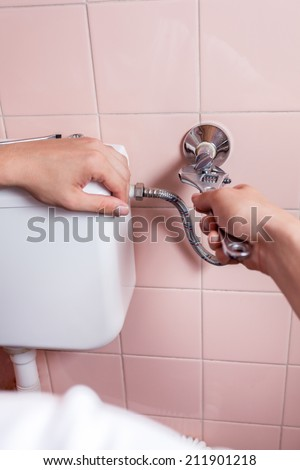 Close-up of a hands repairing toilet, vertical - stock photo