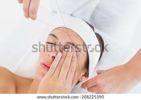 Close up of a hands threading beautiful woman's eyebrow - stock photo
