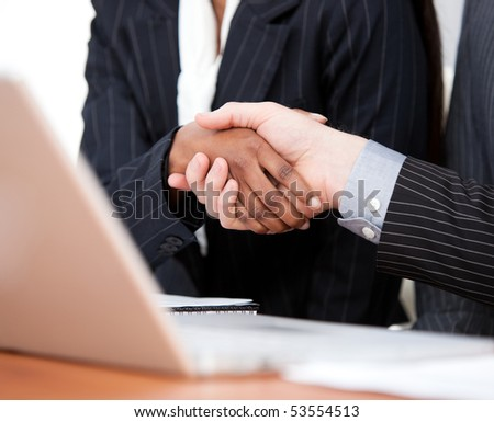 Close-up of a handshake between two businessmen with laptop in the office