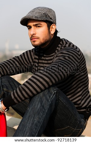 close up of a handsome and confident man wearing sweater and cap in outdoor - stock photo