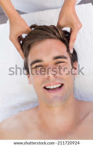 Close -up of a handsome young man receiving head massage at spa center - stock photo
