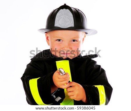 Close-up of a happy, adorable preschool fireman aiming his hose at you.  Isolated on white. - stock photo