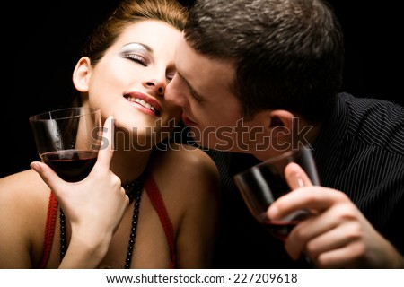 Close up of a happy couple holding wine glasses - stock photo