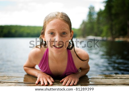 close up of a happy girl on a cottage dock at the lake - stock photo