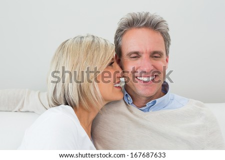 Close-up of a happy loving man and woman sitting in living room at home