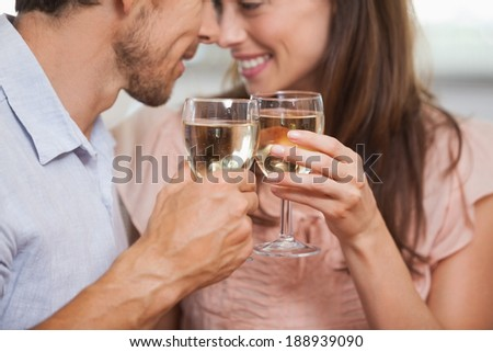 Close-up of a happy loving young couple toasting wine glasses - stock photo