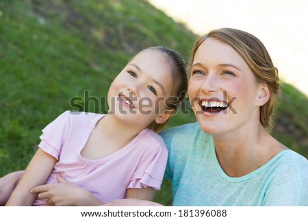 Close-up of a happy mother and daughter at the park - stock photo