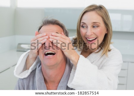 Close-up of a happy woman covering man's eyes in the kitchen at home - stock photo