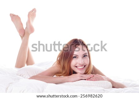 Close up of a happy young woman smile looking at camera while lying on the bed, isolated on white background , caucasian beauty - stock photo