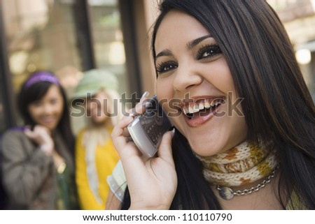 Close-up of a happy young woman talking on cell phone with friends in background - stock photo