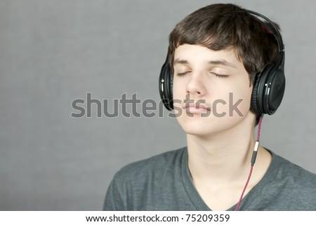 Close-up of a headphone wearing teen meditating. - stock photo