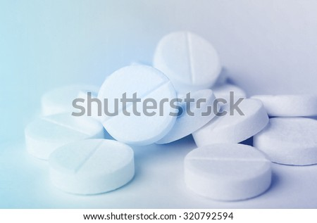 Close up of a heap of white medicine pills on white surface. - stock photo