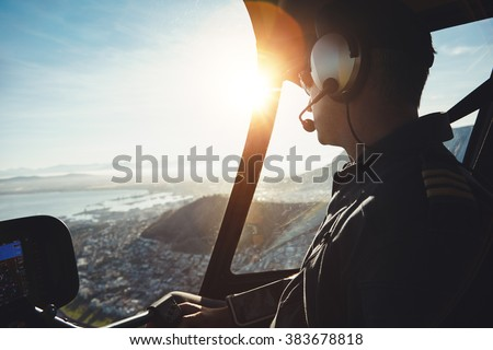 Close up of a helicopter pilot flying aircraft over a city on a sunny day - stock photo