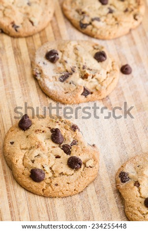 close up of a home made chocolate chip cookie on a wooden cutting board