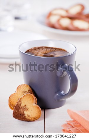 Close up of a hot cup of coffee with cookies