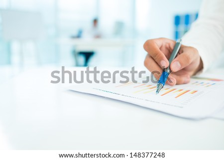 Close-up of a human hand making a strategy analysis on the foreground - stock photo