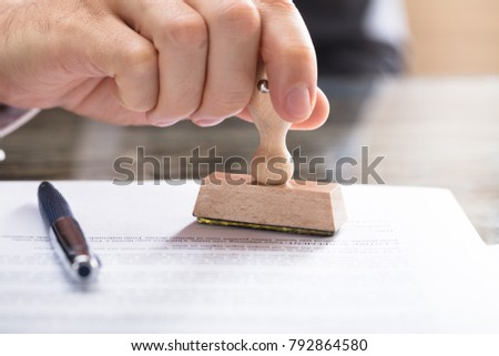 Close-up Of A Human Hand Stamping Document On Desk