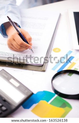 Close-up of a human hand taking notes with pen - stock photo