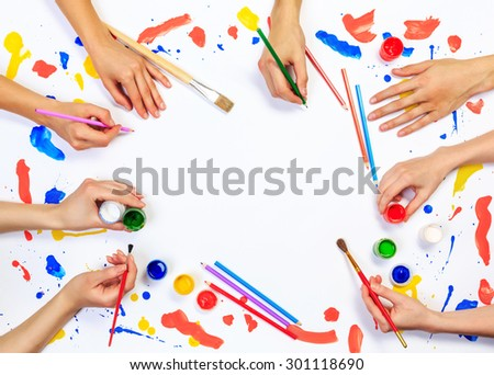 Close up of a human hands painting with gouache on white paper - stock photo