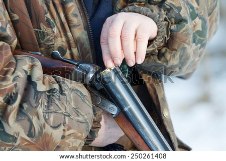 Close-up of a hunter loading his old russian double-barreled side by side shotgun in winter forest - stock photo