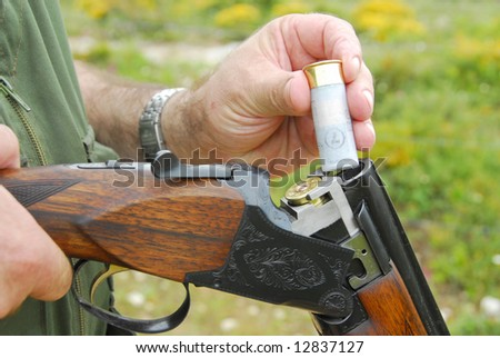 Close up of a hunter loading his weapon - stock photo