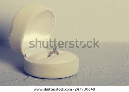 Close-up of a jewelry box with elegant ring from which one with a diamond, symbol of engagement and elegance, vintage style effect picture  - stock photo