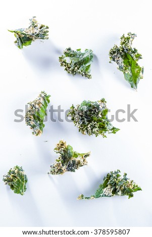 close up of a kale chip covered with melted parmesan cheese and spices on a white background