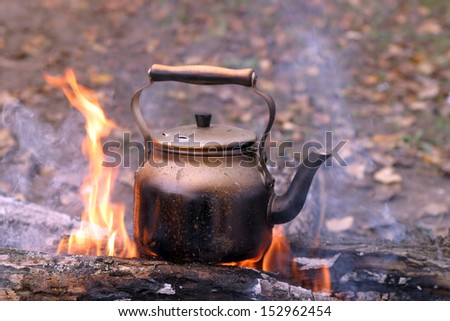 close-up of a kettle on the fire in the autumn - stock photo