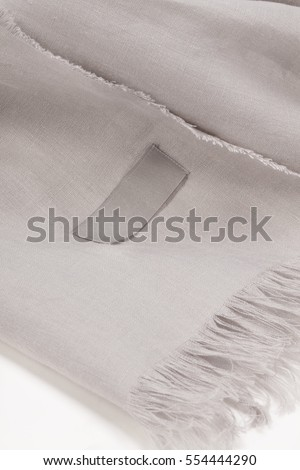 Close up of a linen scarf with tassels and empty tag on white background