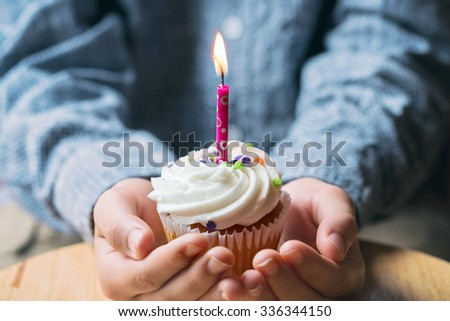 close up of a lit up birthday candle in a cupcake held by a person - stock photo