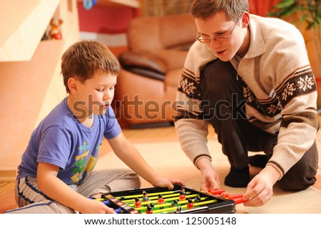 Close-up of a little boy and his father playing board soccer game sitting on floor. - stock photo