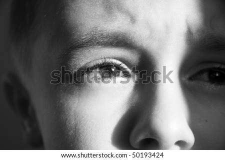 close up of a little boy with tears in his eyes - stock photo