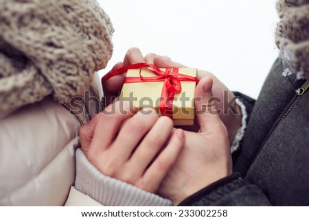 Close-up of a little gift box in hands of lovers - stock photo
