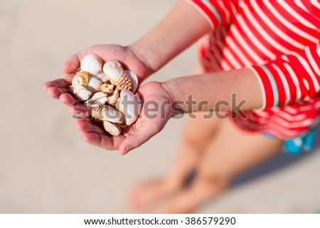 Close up of a little girl holding sea shells in her hands. - stock photo