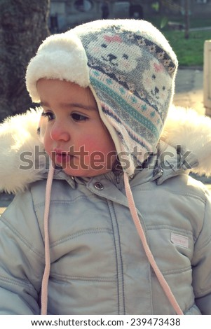Close-up of a little girl outdoors (in the park) wearing warm winter clothes and a cap, on a sunny day. Retro style. - stock photo
