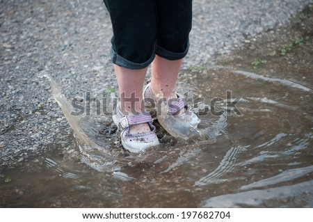 Close up of a little girl's filthy legs as she jumps in a puddle, making a huge splash and wave - stock photo