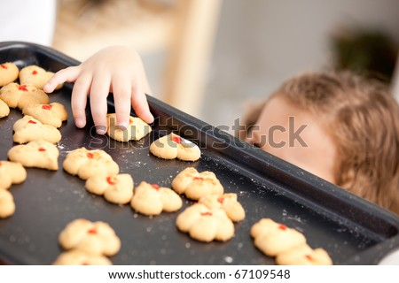 Close up of a little girl taking a cookie behind her mother's back - stock photo